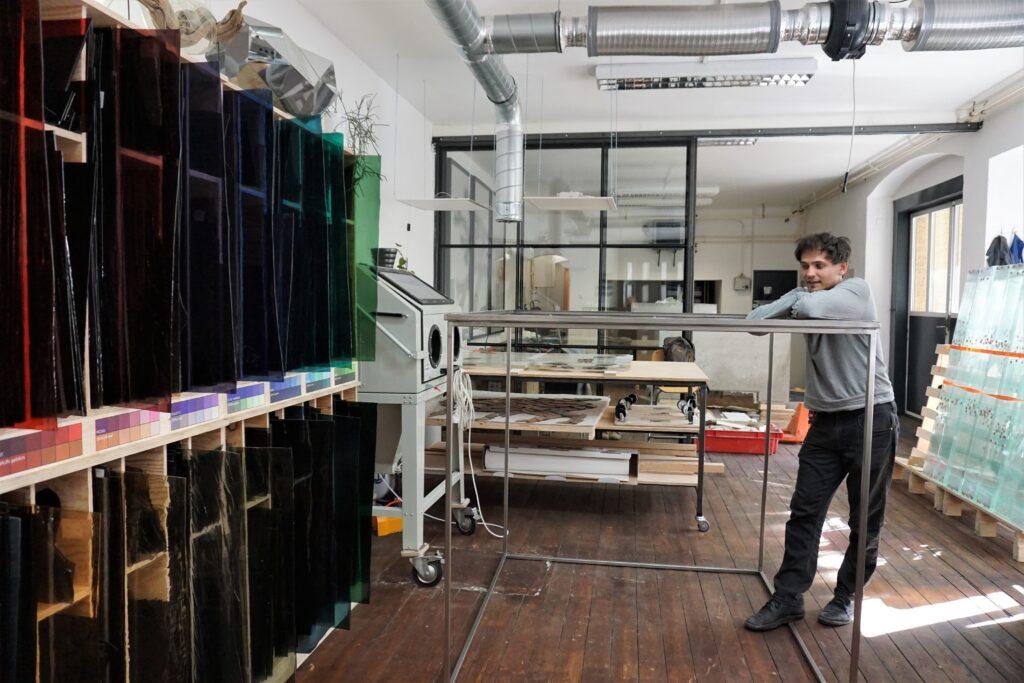 Das Bild zeigt den Künstler Thomas Medicus in seinem Atelier. Er lehnt an einem Stahlrahmen. In der Umgebung sieht man Glas in unterschiedlichen Farben.