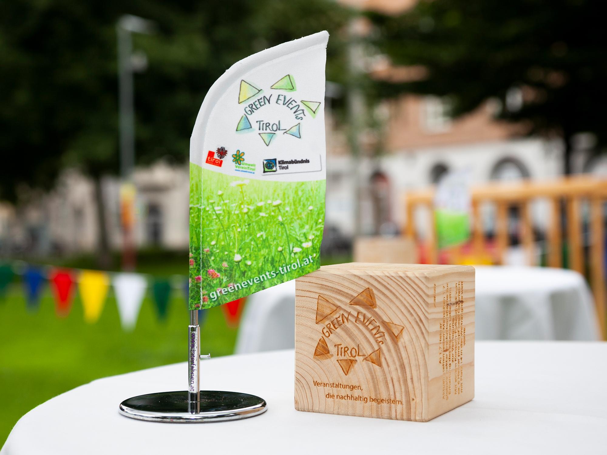 Green Events Tirol Fahne am Tisch des Krapoldi.